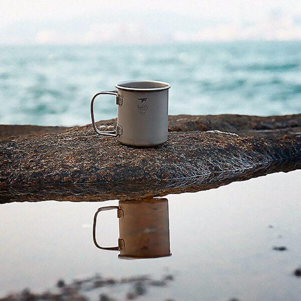 Keith Titanium Mug With Lid 400 ml på en strand vid havet.